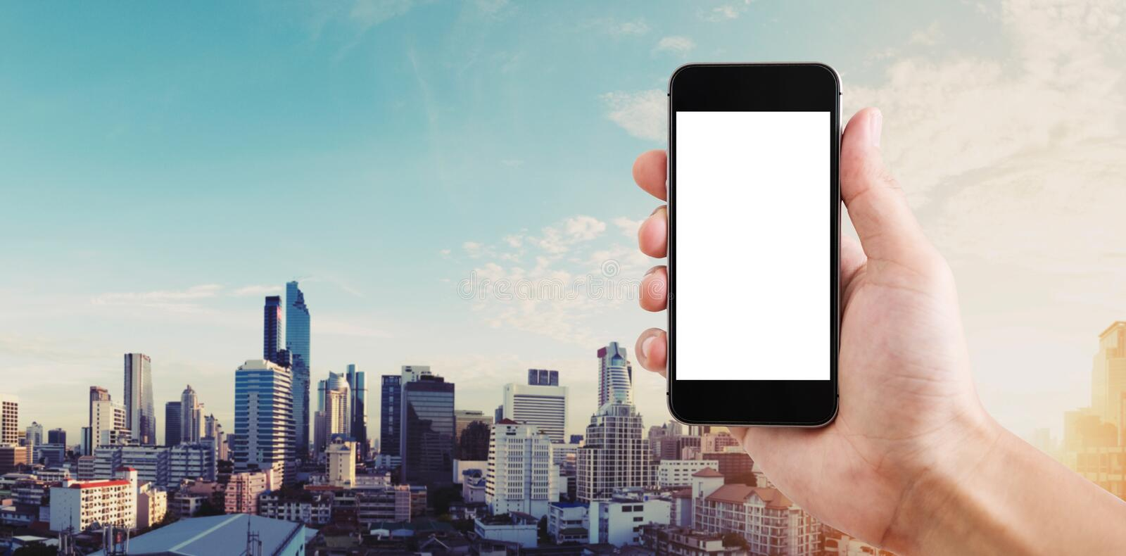 Hand holding mobile smart phone blank white screen, panoramic Bangkok city in sunrise royalty free stock photography