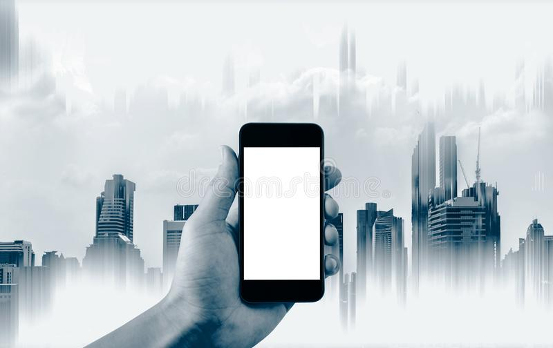 Hand holding mobile smart phone, empty white screen and abstract buildings background. S royalty free stock photography