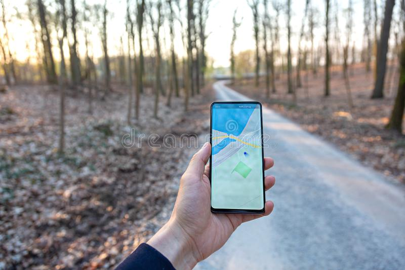 Hand holding a mobile telephone showing a gps map in a forest background royalty free stock photo