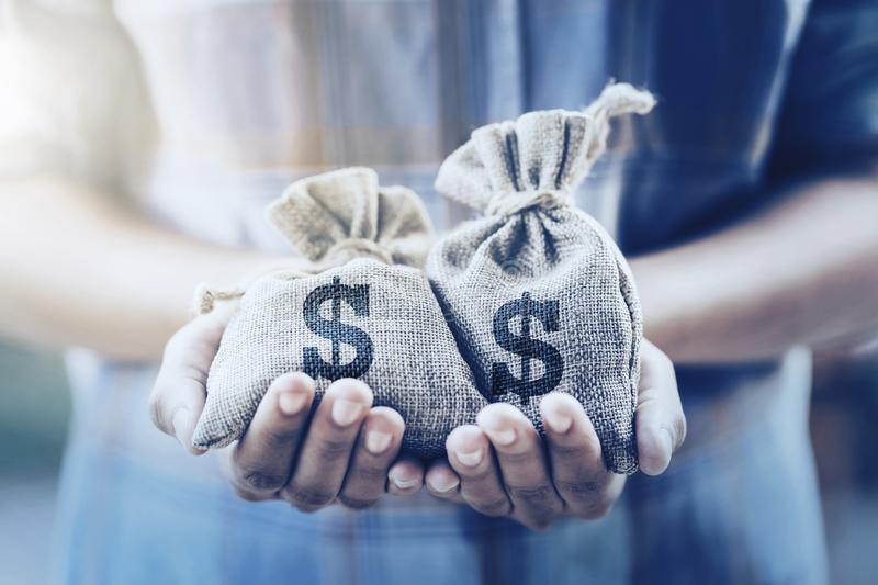 Hand holding money bag. concept saving finance and accounting. Business, background, white, dollar, loan, investment, isolated, give, new, man, success, wealth royalty free stock image