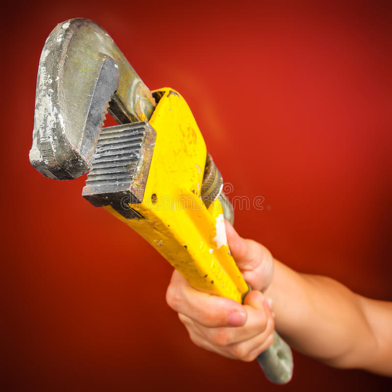 Hand holding a monkey wrench. On a bright red bckground royalty free stock photography