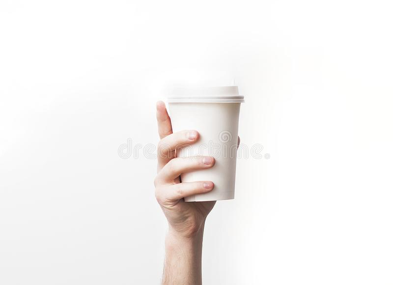 Hand holding a mug, Paper Coffee Cup with delicious coffee in a cafe on a white background, mock up, blank, your cafe shop desig royalty free stock photography