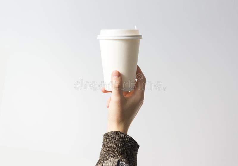 Hand holding a mug, Paper Coffee Cup with delicious coffee in a cafe on a white background, mock up, blank, your cafe shop desig royalty free stock photo