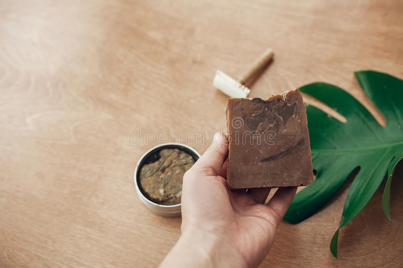 Hand holding natural handmade soap on background of solid shampoo bar, reusable razor on wood with green monstera leaf. Zero waste. Plastic free beauty royalty free stock image