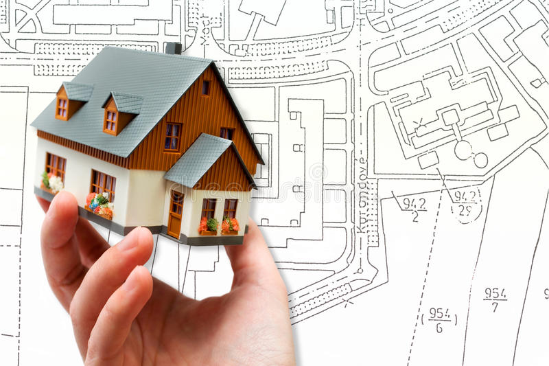Hand holding new model house and architecture blueprint plan. Project royalty free stock image