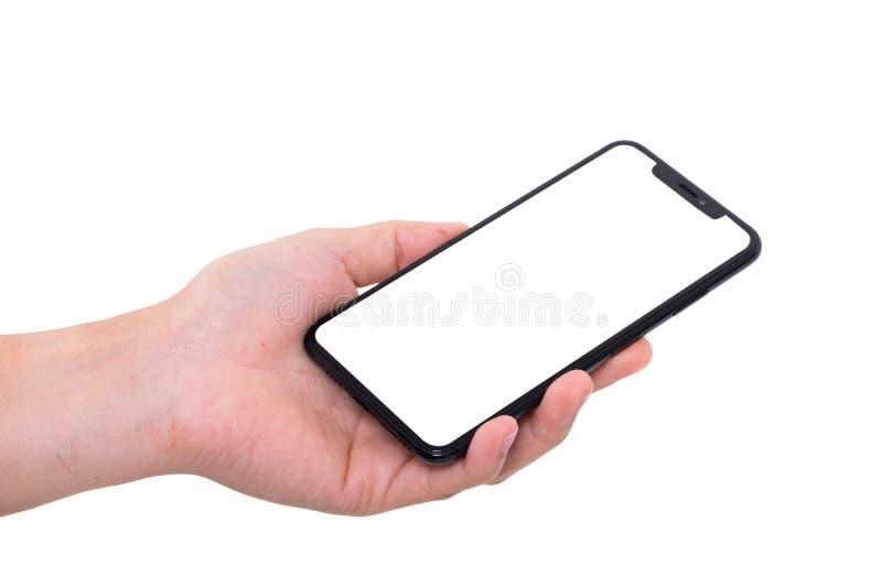 Hand holding new smartphone on white background stock image