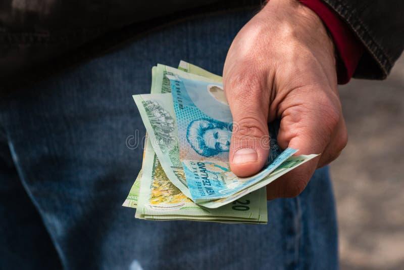 Hand holding New Zealand dollars stock photos