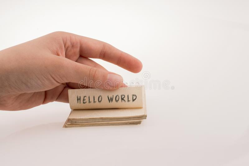 Hand holding a notebook page with HELLO WORLD wording stock image