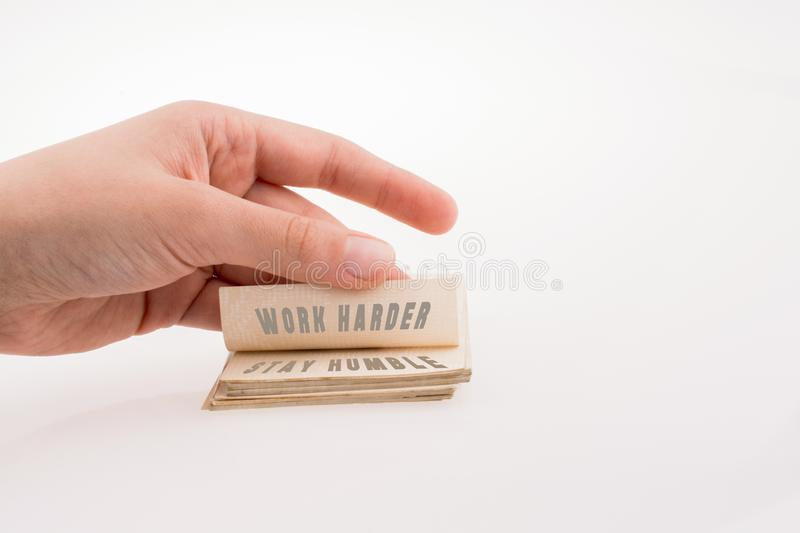 Hand holding a notebook with WORK HARDER STAY HUMBLE text royalty free stock photography