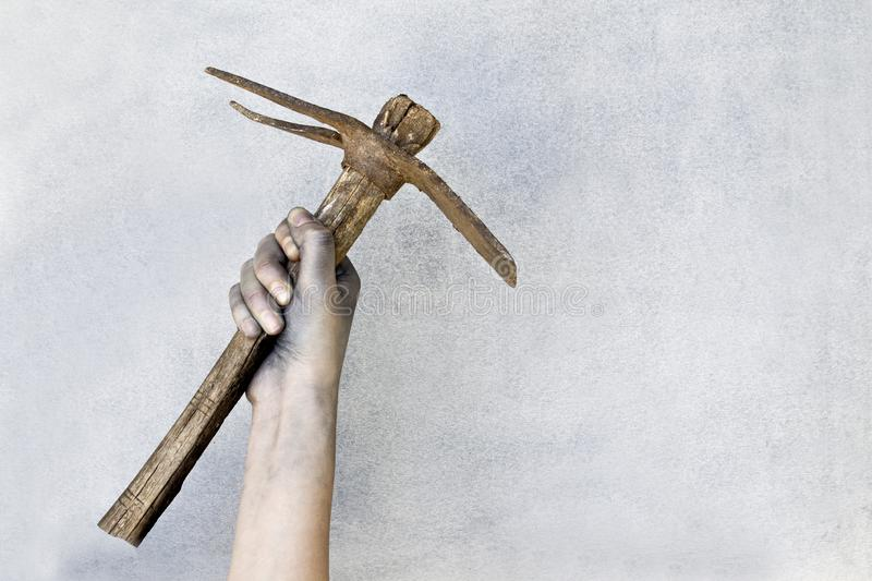 Hand holding a old pickaxe on gray background. stock photos