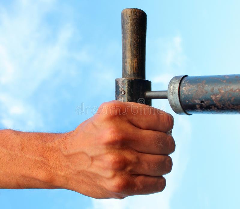 Hand holding the old pump by the handle royalty free stock photo
