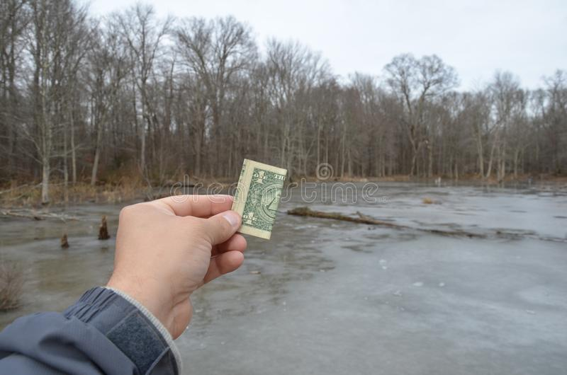 Hand holding one dollar bill in wetland area with frozen water. Hand holding one dollar bill or money in wetland area with frozen water and trees stock photos