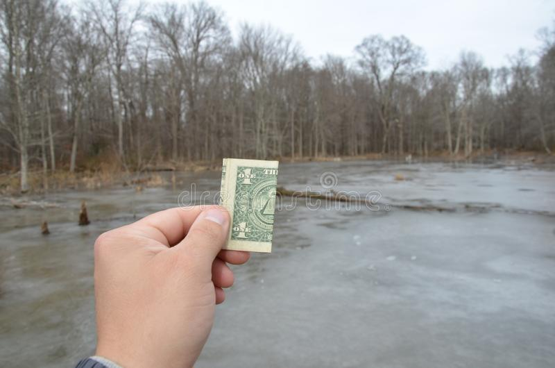 Hand holding one dollar bill in wetland area with frozen water. Hand holding one dollar bill or money in wetland area with frozen water and trees royalty free stock photo