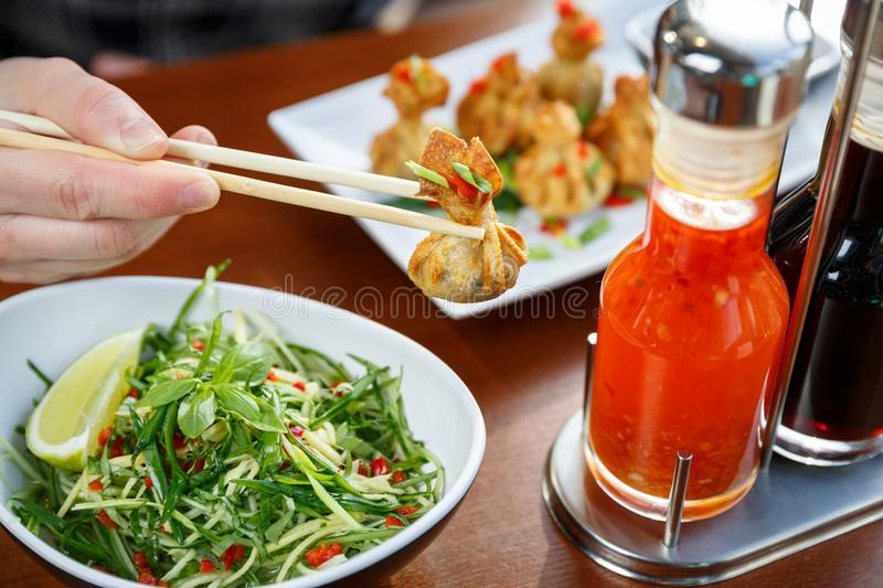 Hand holding one fried wonton with sticks. With vegatable salad and set of sauses standing on a table royalty free stock images