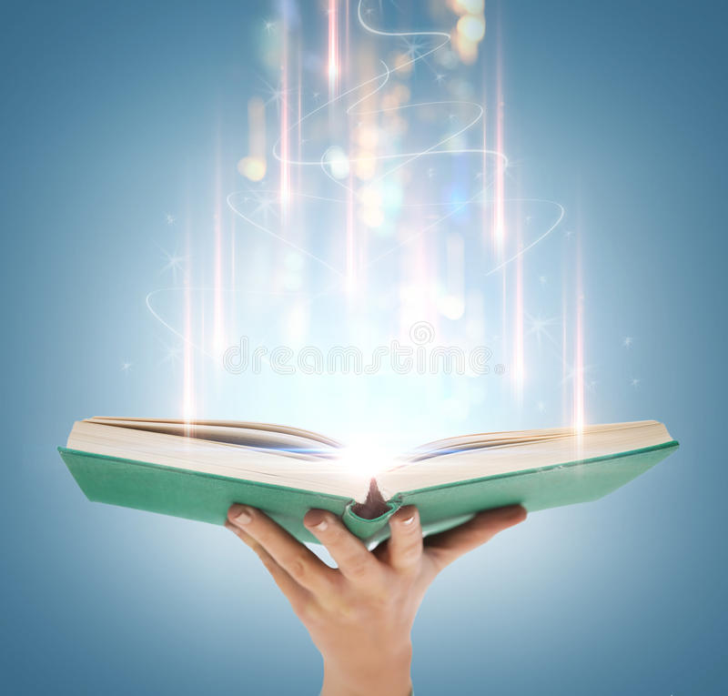 Hand holding open book with magic lights royalty free stock images