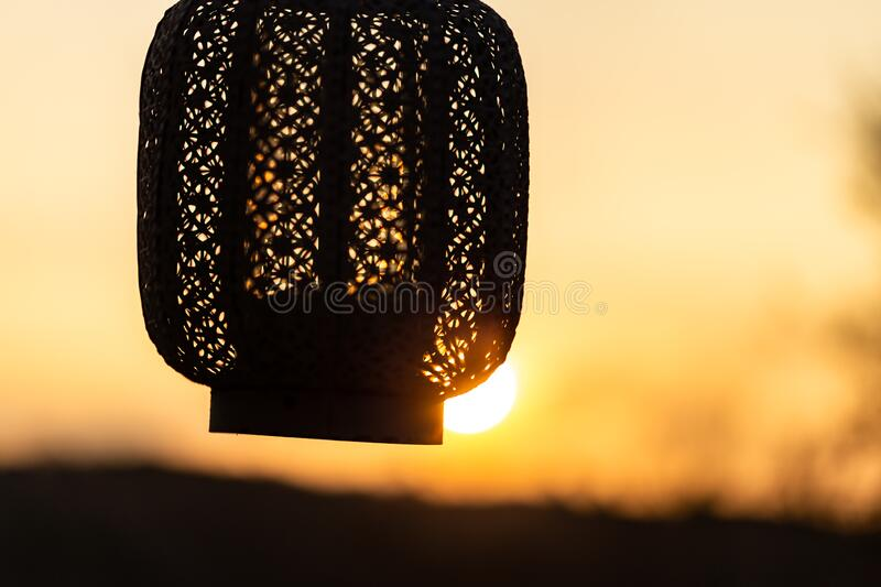 Hand holding oriental lantern with candle while sunset. Sun is shining through the lamp.  stock photo