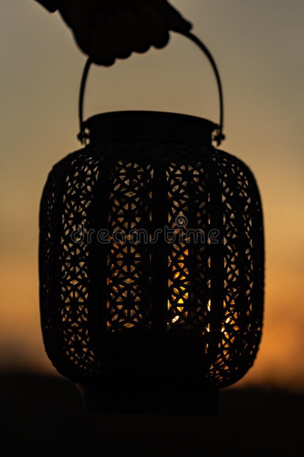 Hand holding oriental lantern with candle while sunset. Sun is shining through the lamp.  stock images