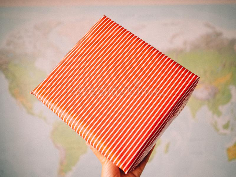Hand holding a package wrapped. In red wrapping paper to celebrate a special day. Image with unfocused background to write a text royalty free stock photos