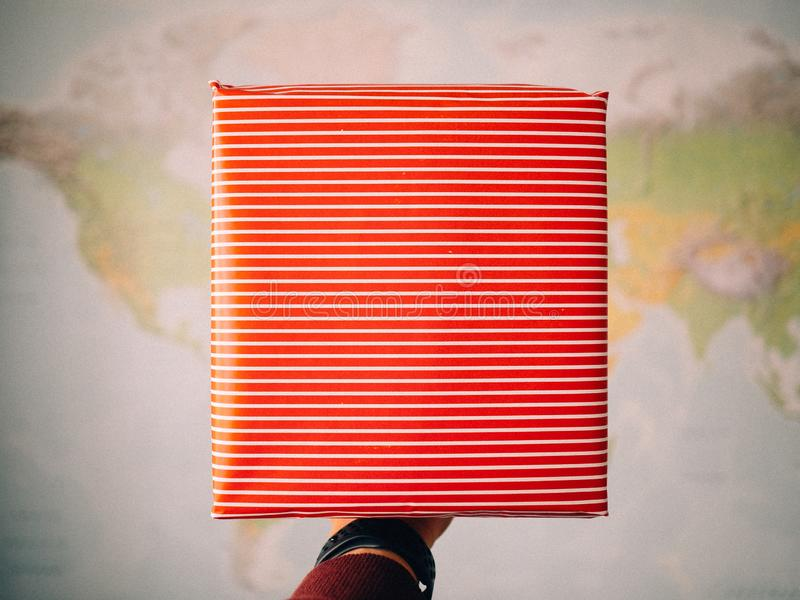 Hand holding a package wrapped. In red wrapping paper to celebrate a special day. Image with unfocused background to write a text royalty free stock image