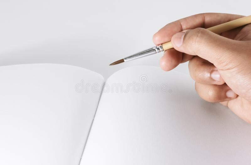 Hand holding paint brush on drawing book royalty free stock photography