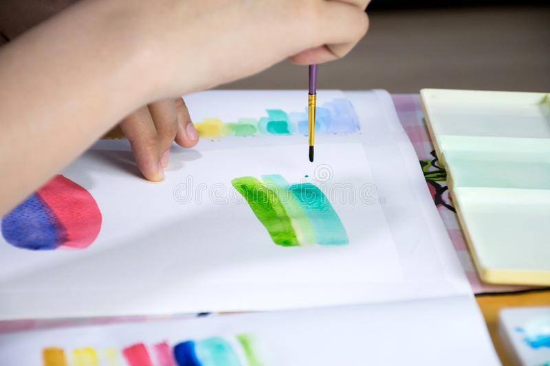 Hand holding paint brush and drawing on white paper with colorful watercolor and equipment stock photo