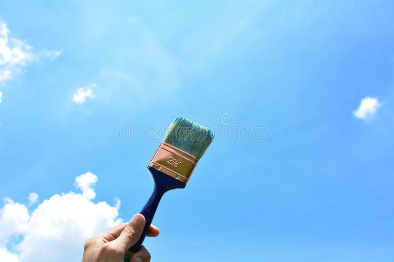 Hand holding the paintbrush on blue sky. stock photos