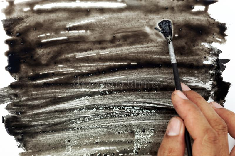 Hand holding paintbrush and paint black color on white paper. royalty free stock photos