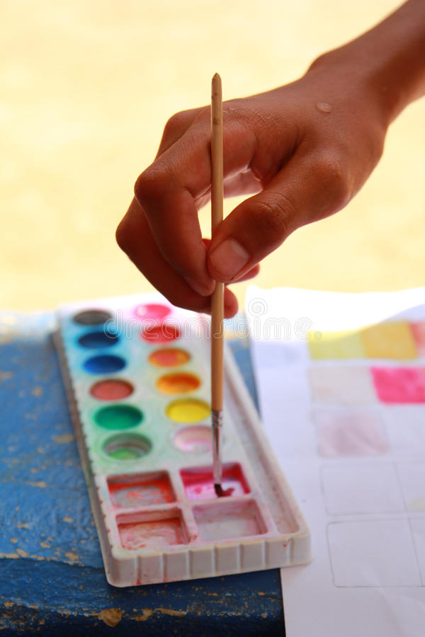 Hand holding the paintbrush. The hand holding the paintbrush to mix color for painting royalty free stock photo