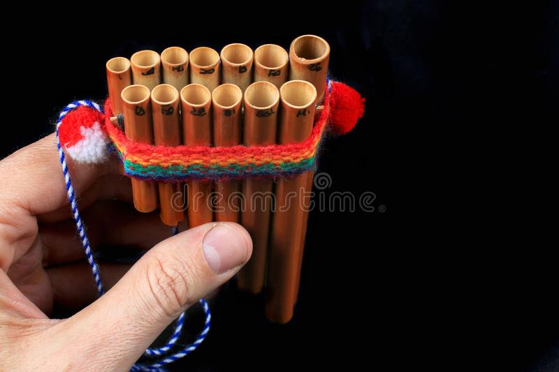 Hand holding a pan flute, on black background royalty free stock photography