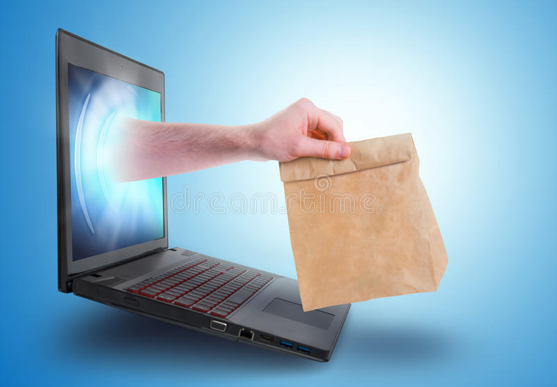 Hand holding a paper bag coming out of a laptop screen stock image