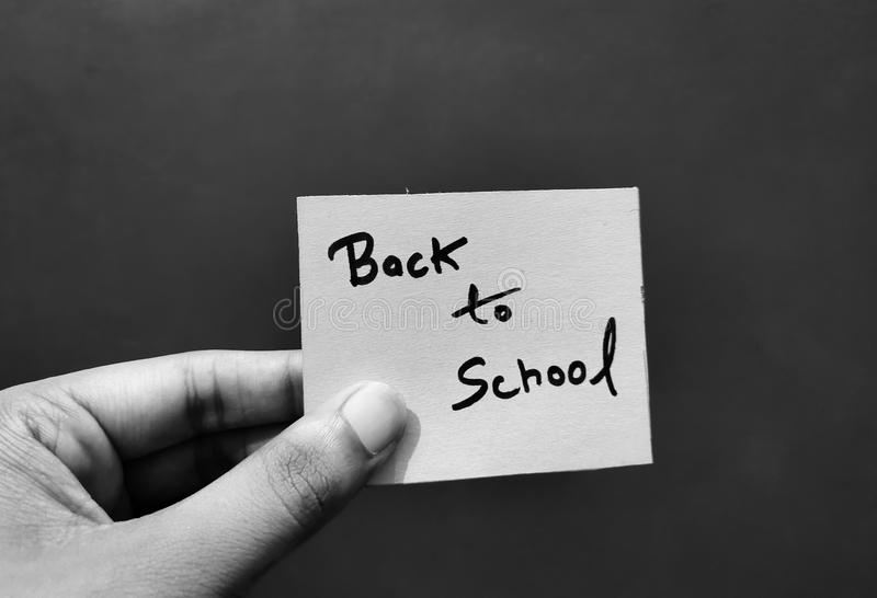 Hand holding a paper card with the words BACK TO SCHOOL. stock image