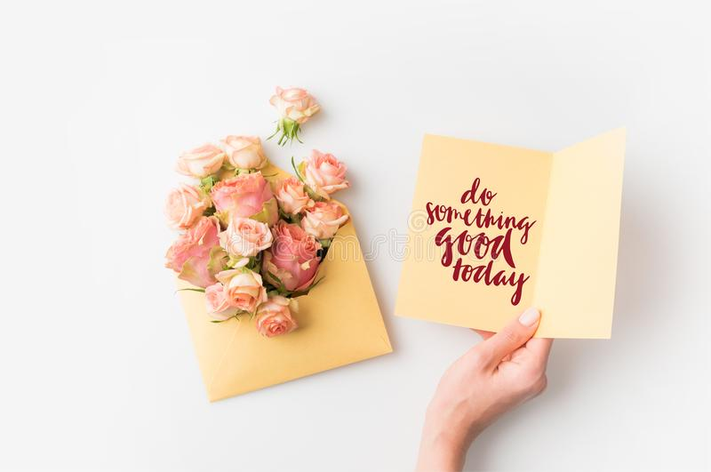 hand holding paper with DO SOMETHING GOOD TODAY inscription beside pink flowers in envelope isolated on white stock photography
