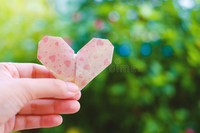 Hand holding paper heart origami on blurred green natural background royalty free stock images