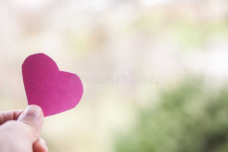 Hand holding paper heart stock image