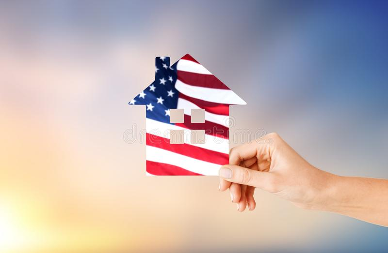 Hand holding paper house in colors of american flag. Patriotism, home and citizenship concept - hand holding paper house in colors of american flag over evening royalty free stock image