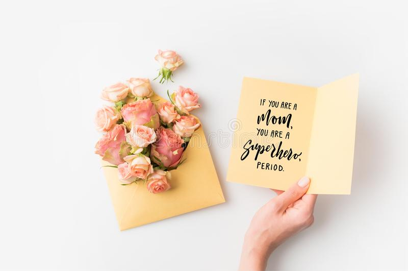 Hand holding paper with mothers day phrase beside pink flowers in envelope isolated on white stock photo