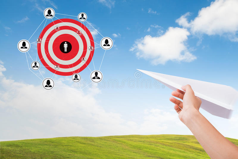 Hand holding paper plane with marketing goals dartboard on sky. stock images
