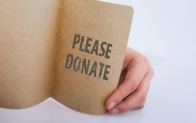 Hand holding a paper with please donate wording stock images