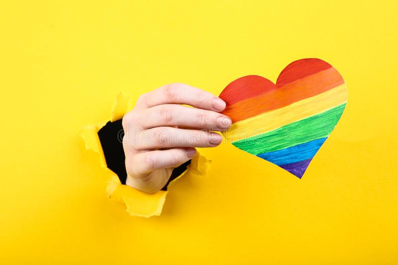 Hand holding paper rainbow heart stock images
