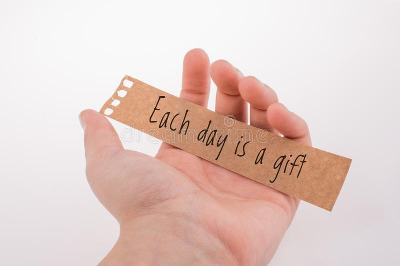 Hand holding a paper with wording Each day is a gifts. Motivational quotes wording  Each dayis a gifts royalty free stock photography