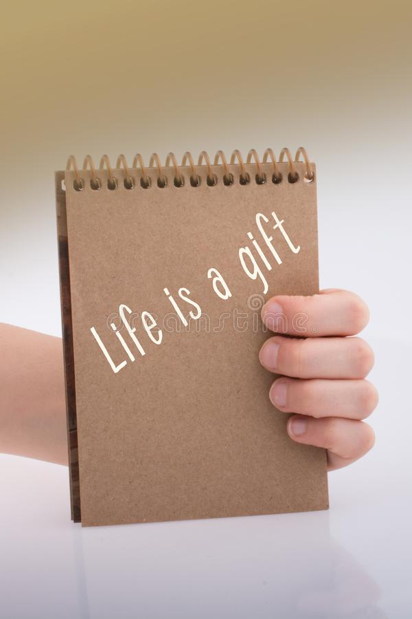Hand holding a paper with wording Each day is a gifts. Motivational quotes wording  Each dayis a gifts stock photography