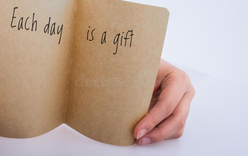 Hand holding a paper with wording Each day is a gifts. Motivational quotes wording Each dayis a gifts stock images