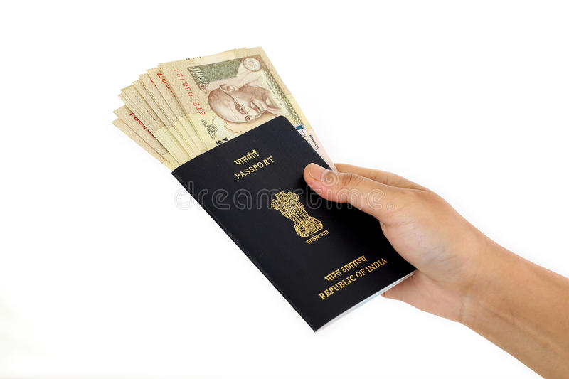 Hand holding passport with Indian currency. Against white background stock images