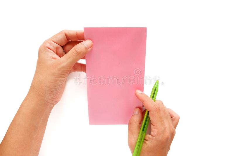 Hand holding a pen and being addressed on a pink envelope royalty free stock images