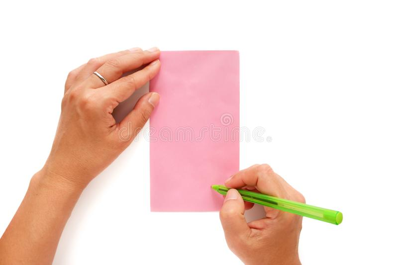Hand holding a pen and being addressed on a pink envelope stock photo