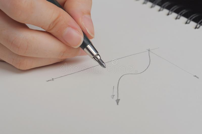 Hand holding pen and drowing graph on white sheet stock photography