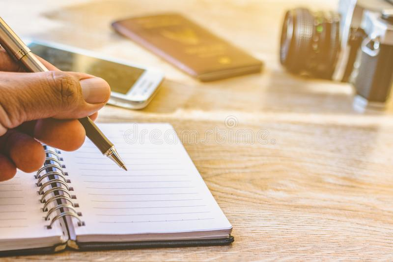 Hand holding a pen and notebook. Men are writing recorded on notebook a daily basis. Camera Phones and Accessories on old wood royalty free stock photography
