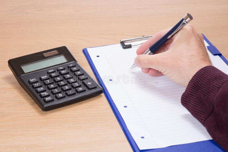 Hand holding a pen over a blank document stock images