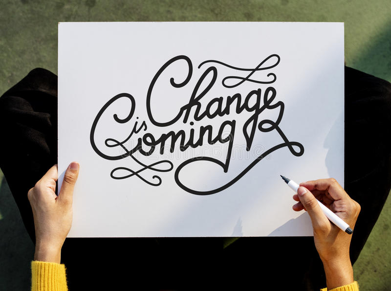 Hand Holding Pen Paper Writing Change is Coming Board Concept stock image