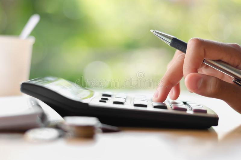 hand holding pen and pressing calculator button for business accounting of finance royalty free stock photo